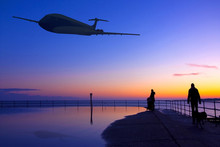 Aeroplane Flying Over The Sea And Land At Sunset