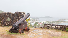 Very Old Rusted Canon Pointing At A Bay