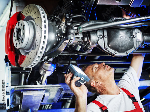 Fotografie, Obraz  Motor mechanic inspecting the engine of a car