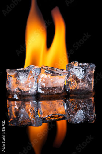 Photo  Ice cubes with flame on shiny black surface