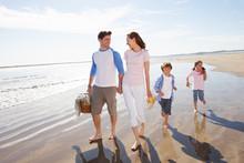Family Walking Along Beach Wit...
