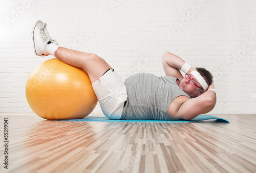 Funny overweight man working out in the gym Fototapeta