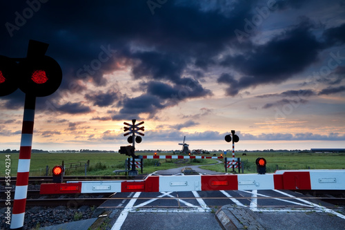 Valokuva  closed rail crossing at sunrise and windmill