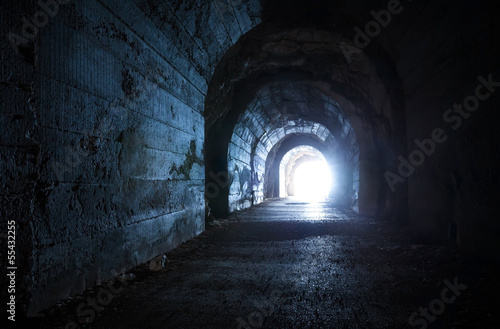 Fotobehang Tunnel Blue glowing exit from dark abandoned tunnel