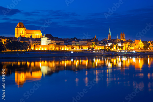 Torun old town at night reflected in the river, Poland