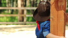 Portrait Of A Little Cowboy Next To A Wooden Fence Paddocks