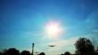 Large passenger airliner landing flying through sun rays