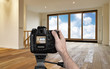 Man photographing empty living room with digital camera