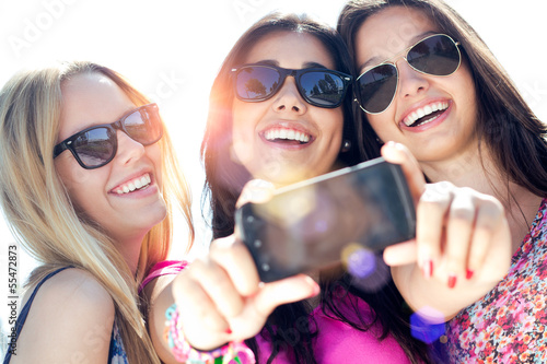 Fotografie, Tablou  three friends taking photos with a smartphone