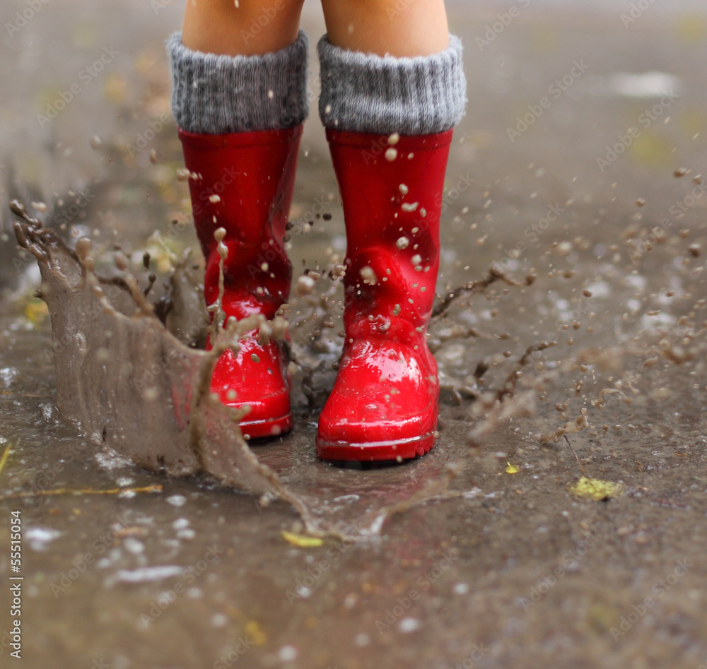 Fototapeta Child wearing red rain boots jumping into a puddle