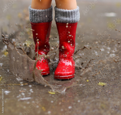 Fotografie, Obraz  Child wearing red rain boots jumping into a puddle