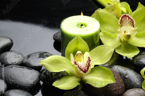 Fotobehang Spa Green orchid and candle on black stones