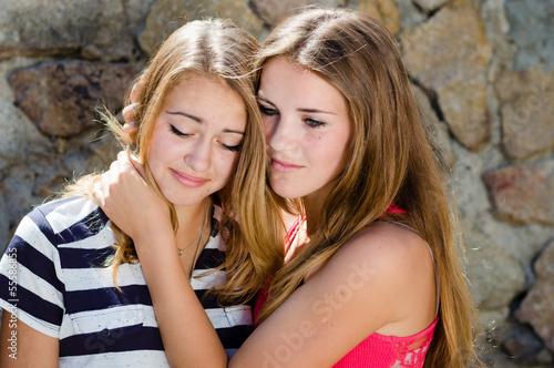 Fotografía  Teenage girl comforting crying friend with warm hug