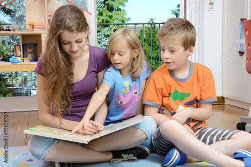 Babysitter schaut Buch mit Kindern Canvas Print