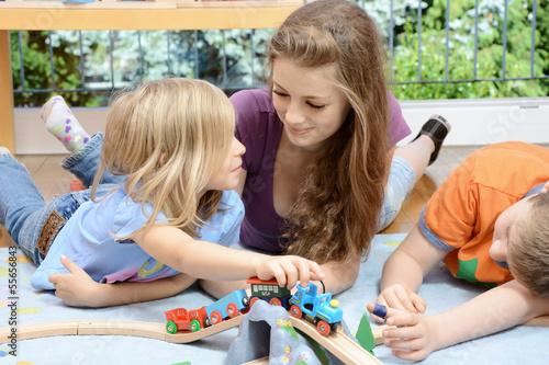 Babysitter spielt mit Kindern Wallpaper Mural