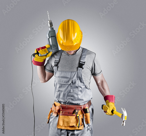 Fotografia  builder in a helmet with a hammer and a drill