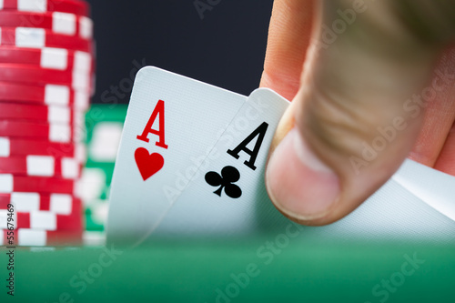 Poker player lifting the corners of two cards плакат