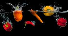 Fresh Vegetables Splashing In Water On Black