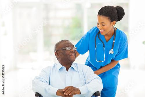 Fotografia african nurse taking care of senior patient in wheelchair
