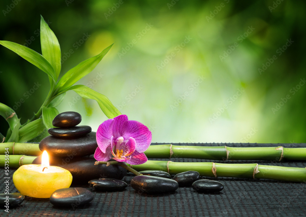 Fototapeta purple orchid, candle, with stones , bamboo on black mat