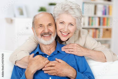 Photo glückliches älteres paar umarmt sich auf dem sofa