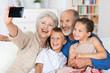 canvas print picture - großeltern fotografieren die familie mit handy