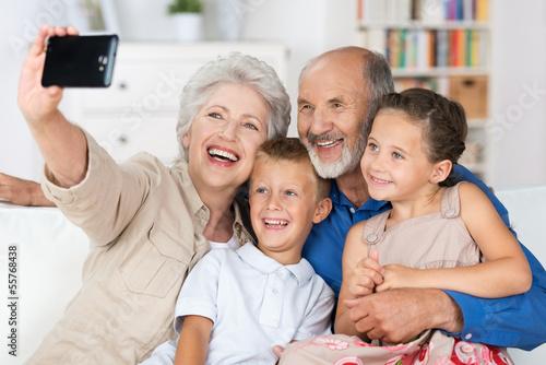 Obraz großeltern fotografieren die familie mit handy - fototapety do salonu
