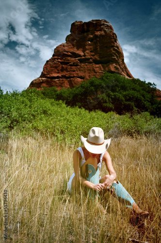Fotografia, Obraz  Woman in cowboy hat and boots in the mountains