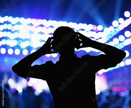 Aluminium Prints Silhouette of DJ wearing headphones and performing at a night club