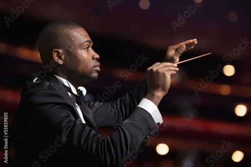 Young conductor with baton raised at a performance  - 55839805