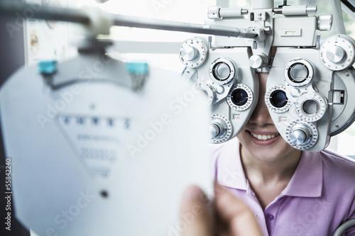 Fotografía  Close-up of optometrist doing an eye exam on young woman