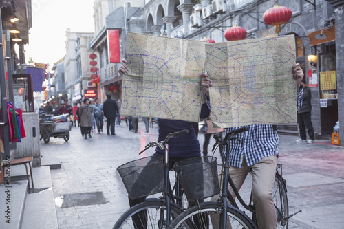 Fotografie, Obraz  Young man and woman on bicycles holding maps.