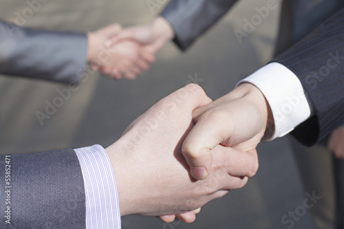 Fototapety, obrazy: Close up of four business people shaking hands