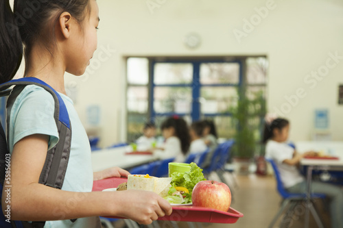 School girl holding food tray in school cafeteria Fototapet