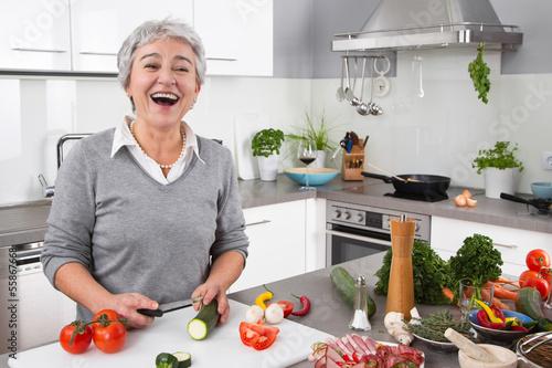 Seniorin - ältere Frau hat Spaß beim Kochen - Gemüse #55867668