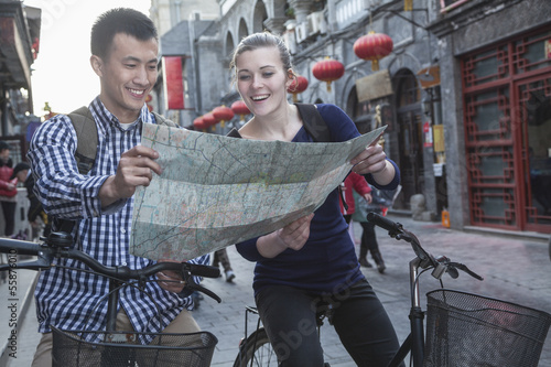 Young man and woman on bicycles, looking at map.