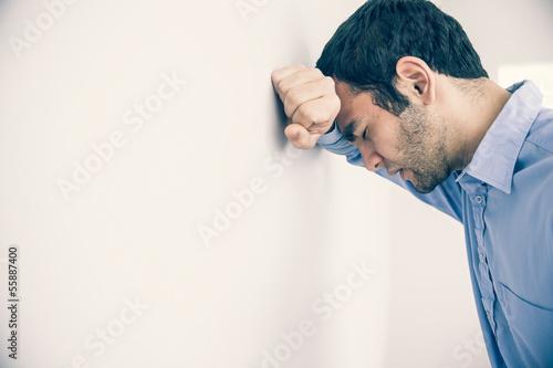 Slika na platnu Depressed man leaning his head against a wall