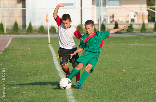 Fotografie, Tablou  kids playing defense on football match