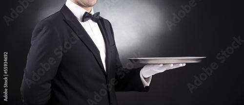 Waiter holding empty silver tray over black background Fototapete