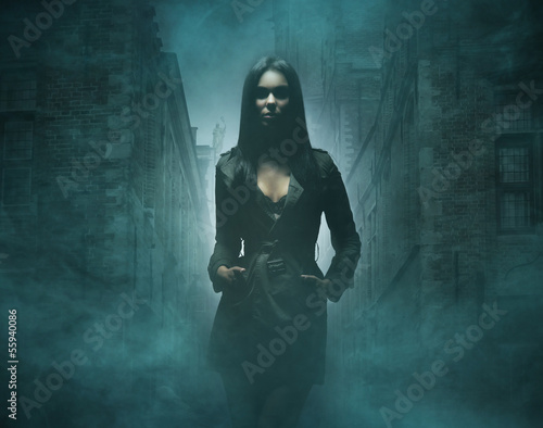 Fashion shoot of a young and sexy brunette in a dark dress Canvas Print