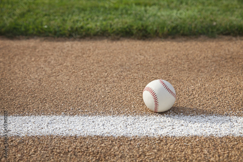 Photo  Baseball on base path with grass infield