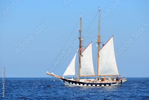 Photo Stands Ship old historical tall ship (yacht) with white sails in blue sea
