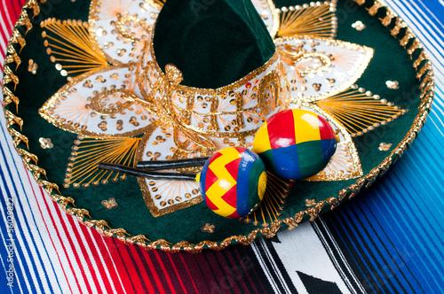Fotografie, Obraz  Mexican sombrero and maracas on a striped poncho