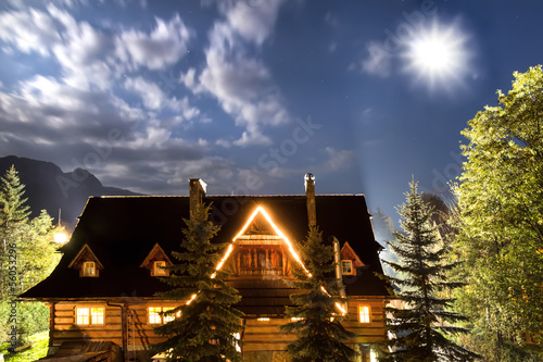 Old country house against sky. Shining moon.