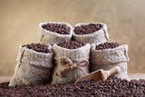 Roasted coffee beans in small burlap bags