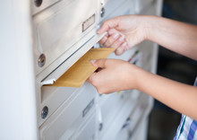 Woman Putting Envelope In Mailbox