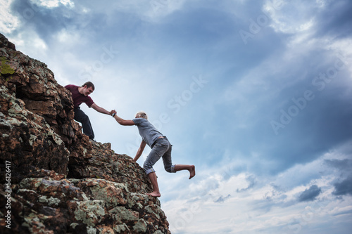 Fotografie, Obraz  Man giving helping hand to friend to climb mountain rock cliff