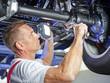 Mechanic in a garage checks a tyre of a car
