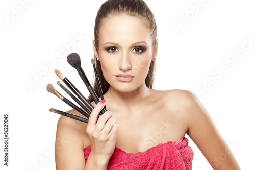 attractive girl is holding in her hand a few makeup brushes