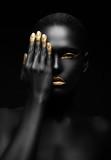 ciemnoskóra kobieta o złotym makijażu. - 56248061